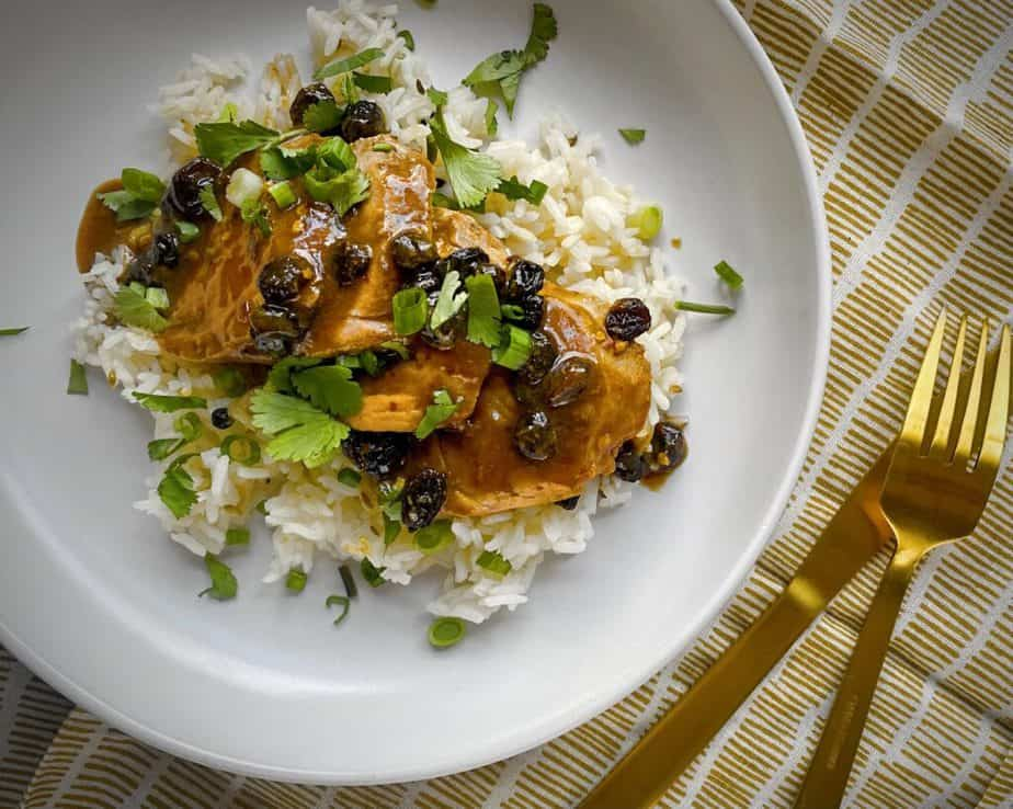 overhead shot of roasted pork tenderloin with ginger raisin pan sauce over rice and garnished with green onions and cilantro