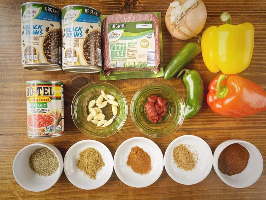 mise en place for easy spicy beef and black bean chili - 2 cans black beans, 1 lb ground beef, 1 yellow onion, 2 bell peppers, 2 jalapeños, tomato paste, garlic cloves, 1 can rotel and assorted spices