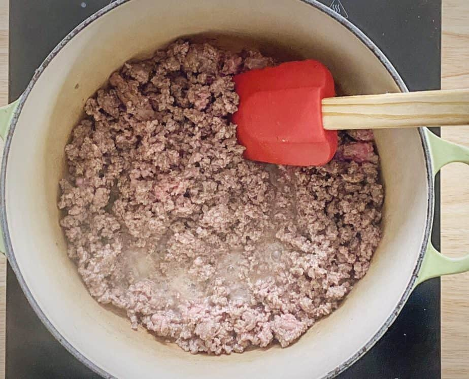 browned ground beef in enameled dutch oven with red silicone spatula