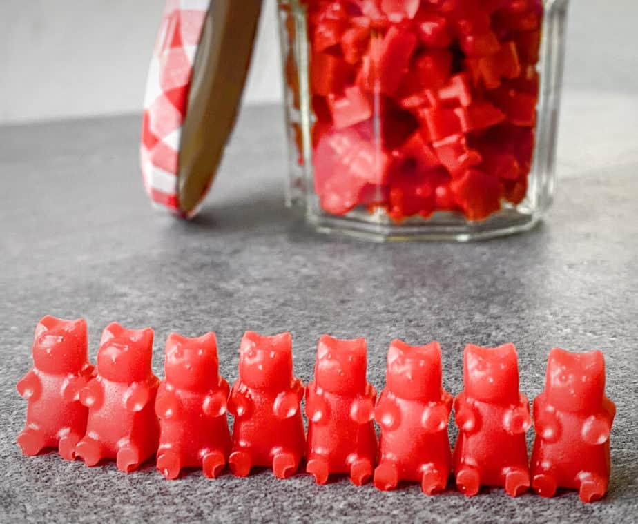 line of 8 homemade cbd gummy bears with a jar of more cbd gummies in the back
