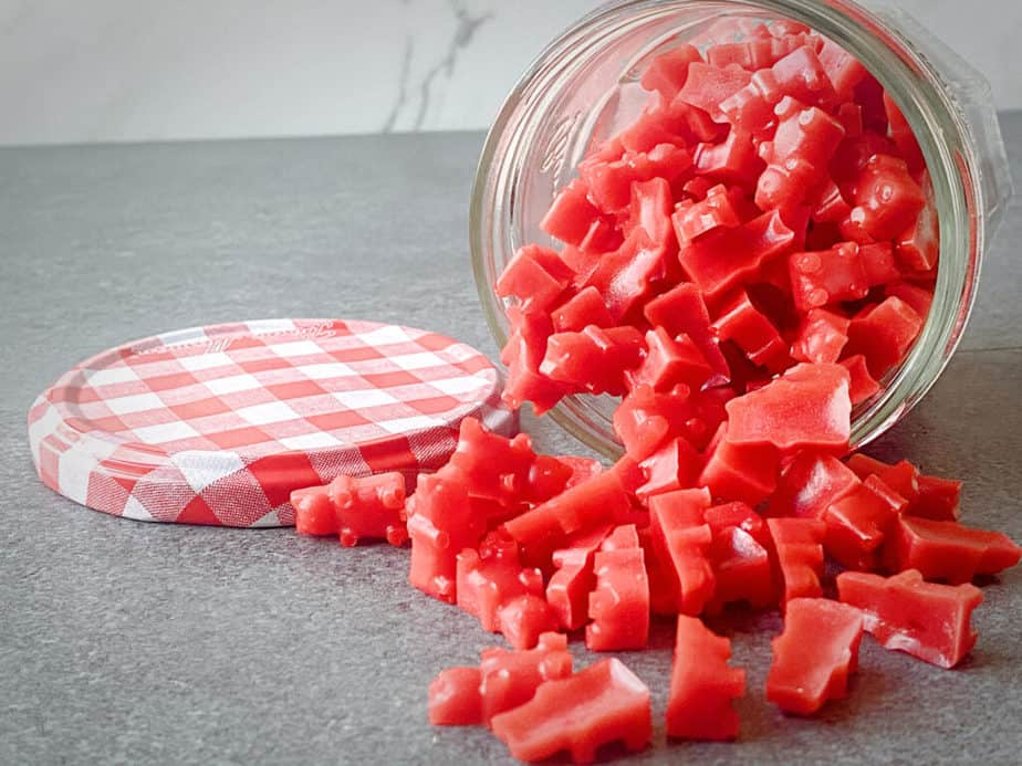 glass jam jar tipped on its side with a bunch of homemade red cbd gummy bears spilling onto a grey tabletop