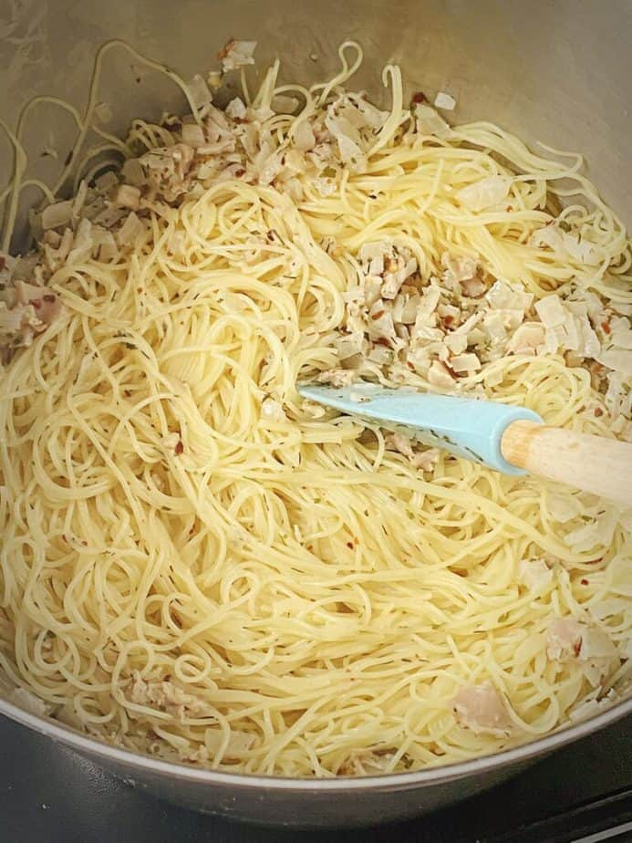 stock pot with cooked noodles and white clam sauce added