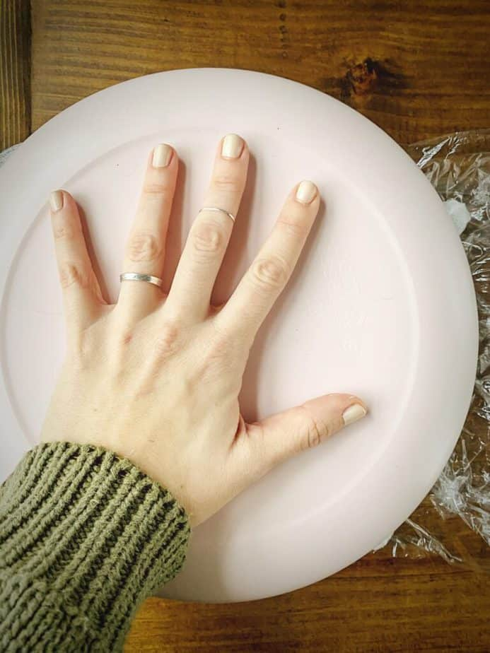 hand securing a pink plate atop coeur a la creme mould