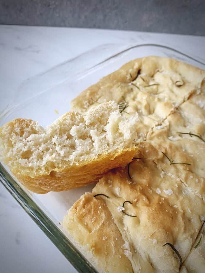 close up shot of a piece of easy homemade focaccia turned on its side to show texture