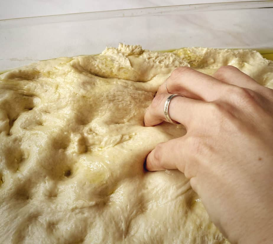 close up of hand pushing all the way through focaccia dough to stretch it
