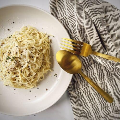 white pasta bowl with a portion of pasta and white clam sauce garnished with parmesan and pepper on a black and white linen