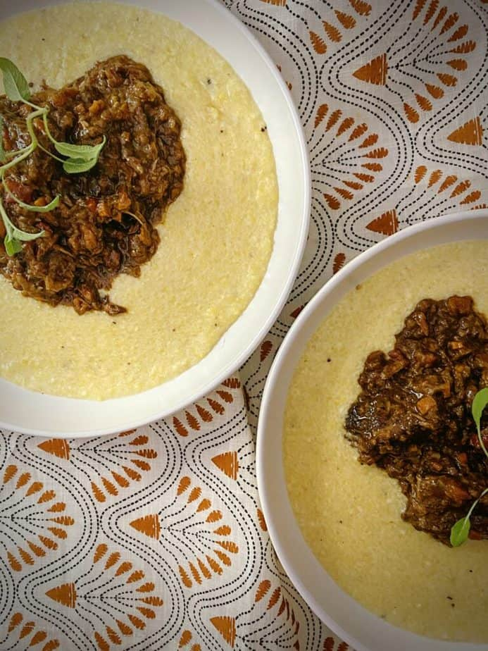overhead shot of two white pasta bowls filled with parmesan polenta and red wine braised beef short ribs on an orange and black embroidered linen