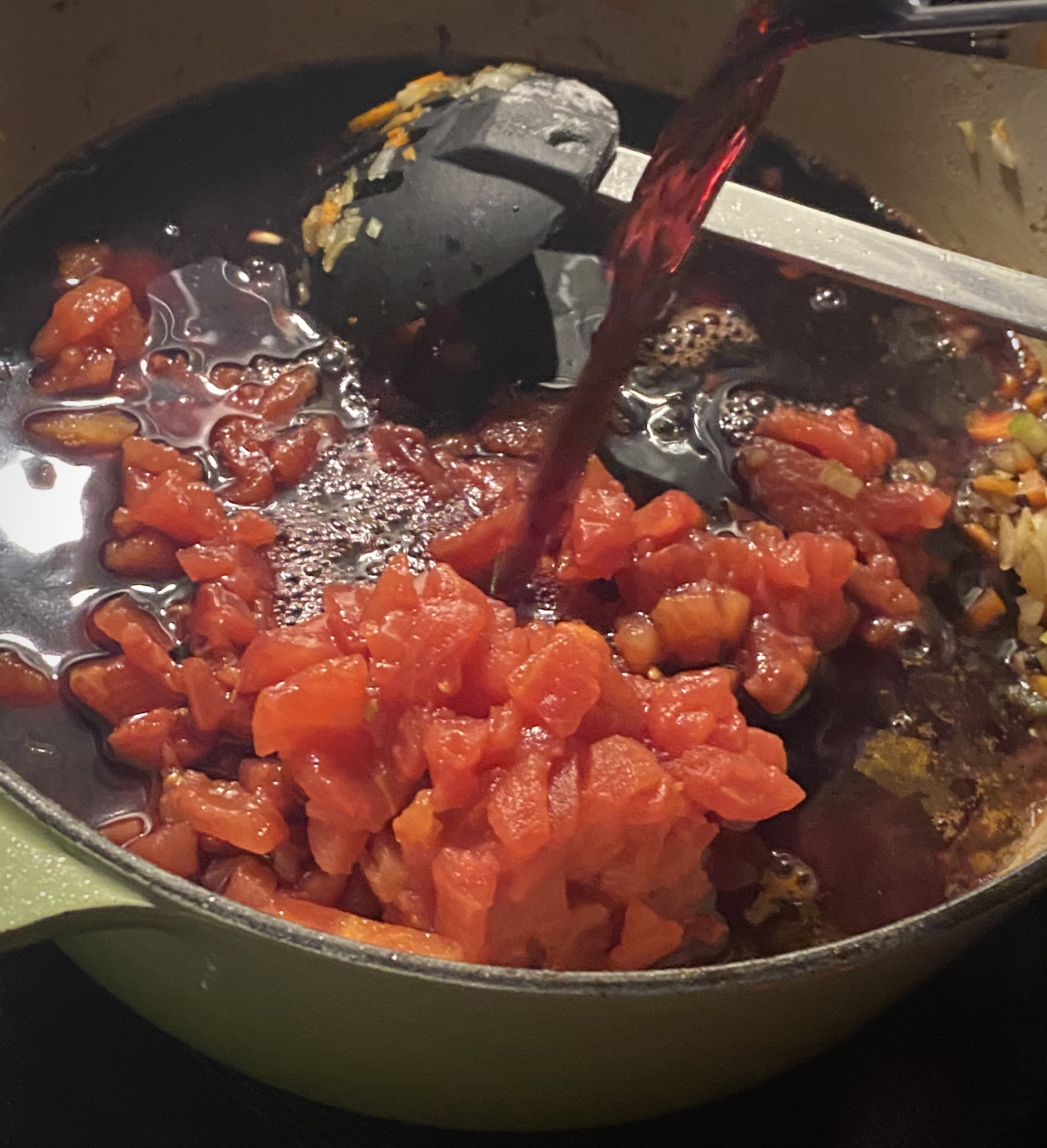 red wine being poured into dutch oven with tomatoes and mirepoix mix for braising short ribs