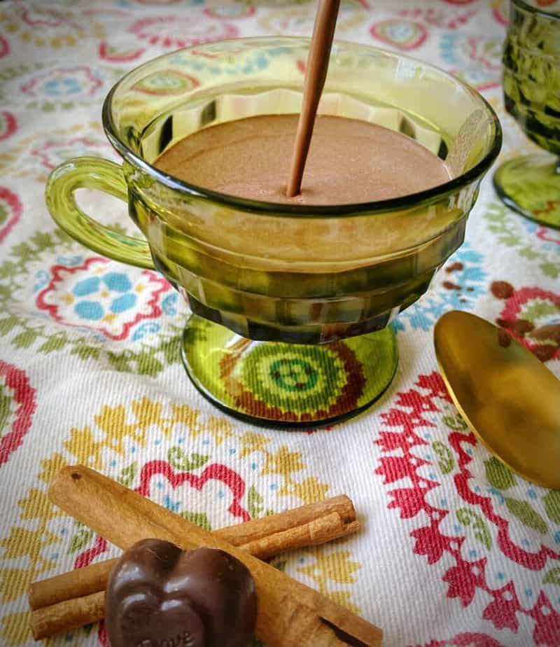 hero shot of spicy aztec sipping chocolate being poured into a clear green footed mug on a colorful printed linen with a gold spoon