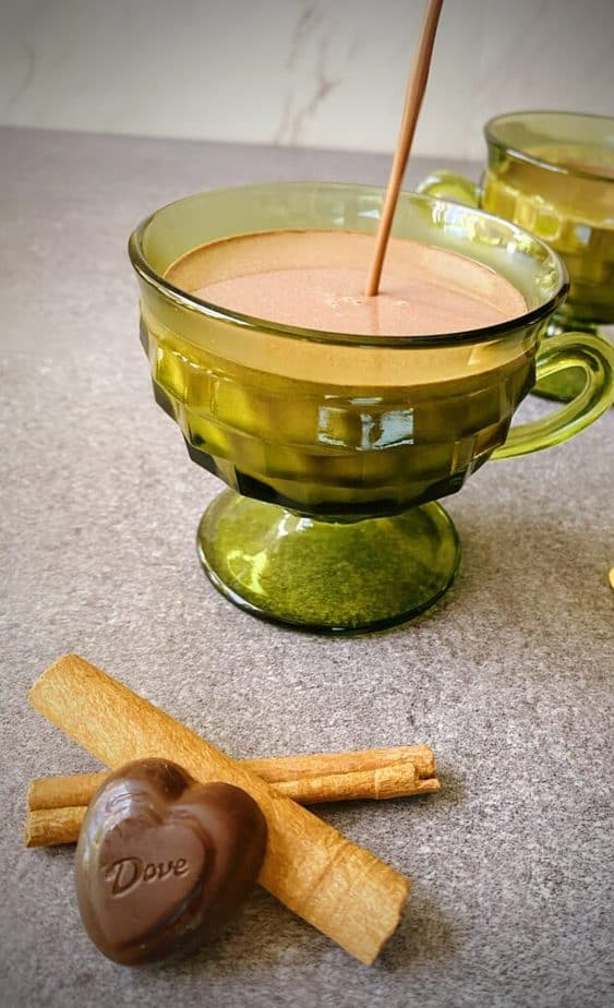spicy hot chocolate being poured into a green footed mug on a grey table with two cinnamon sticks and a chocolate heart