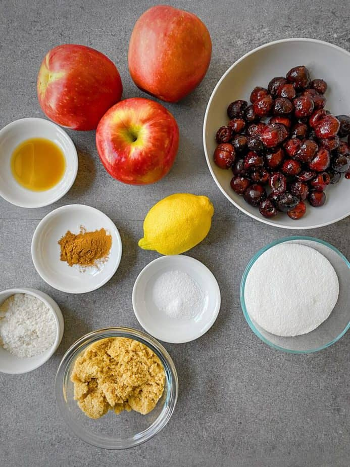 three apples, frozen cherries, vanilla, spices, a lemon, salt, sugar, brown sugar and flour laid out for making cobbler filling