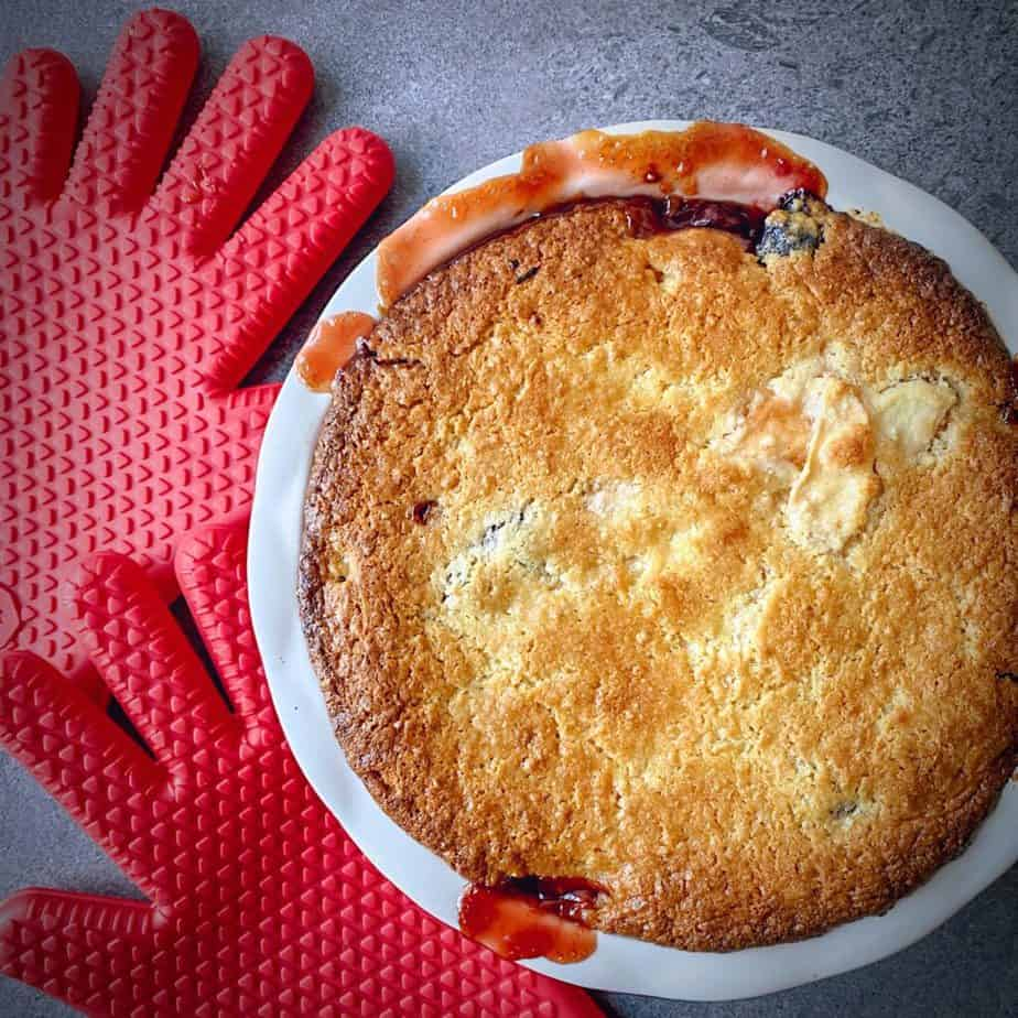 overhead shot of baked apple cherry cobbler on a grey table with red silicone oven mitts