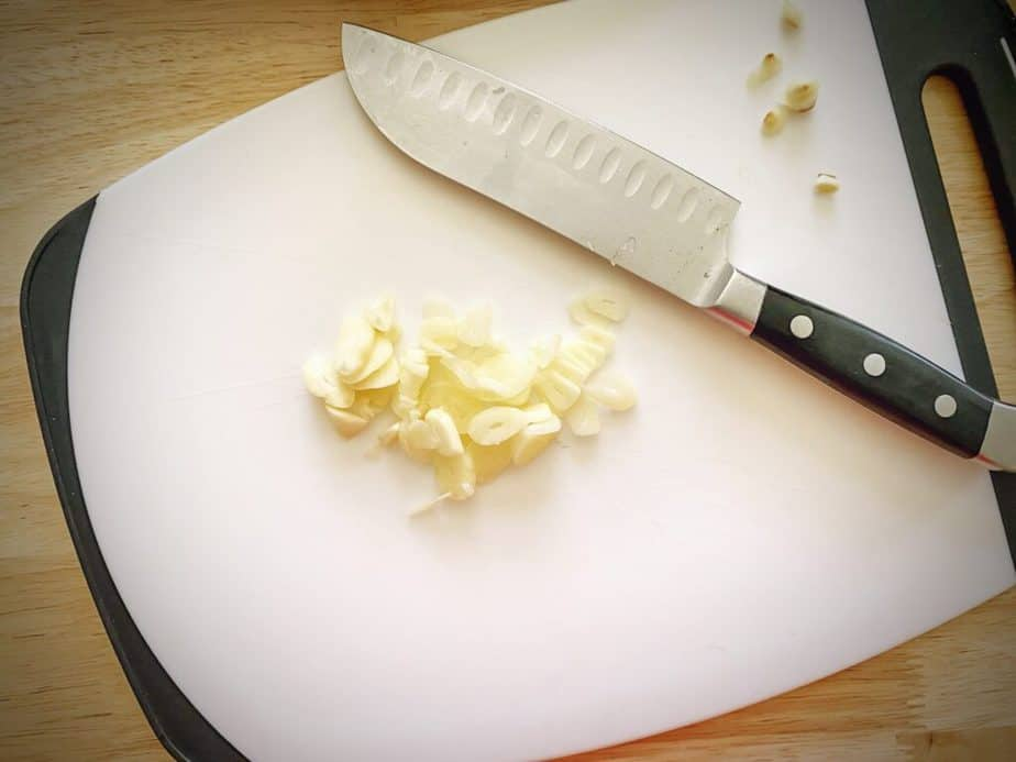sliced garlic on a cutting board with a small chef's knife
