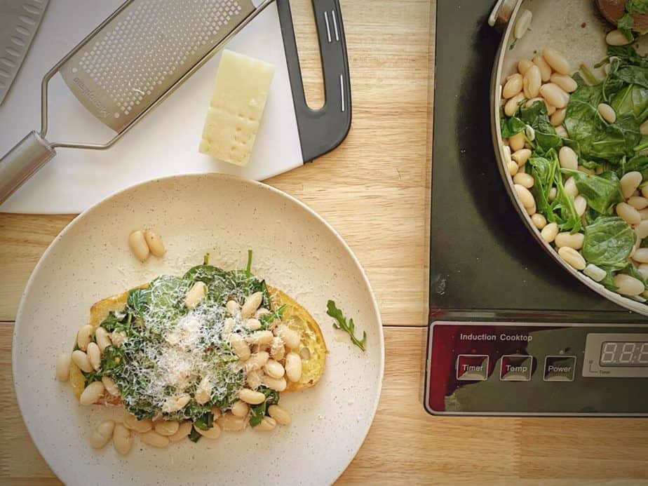 countertop with induction cooktop with sauté pan of beans and greens next to an assembled lunch plate that has been topped with freshly grated parmesan