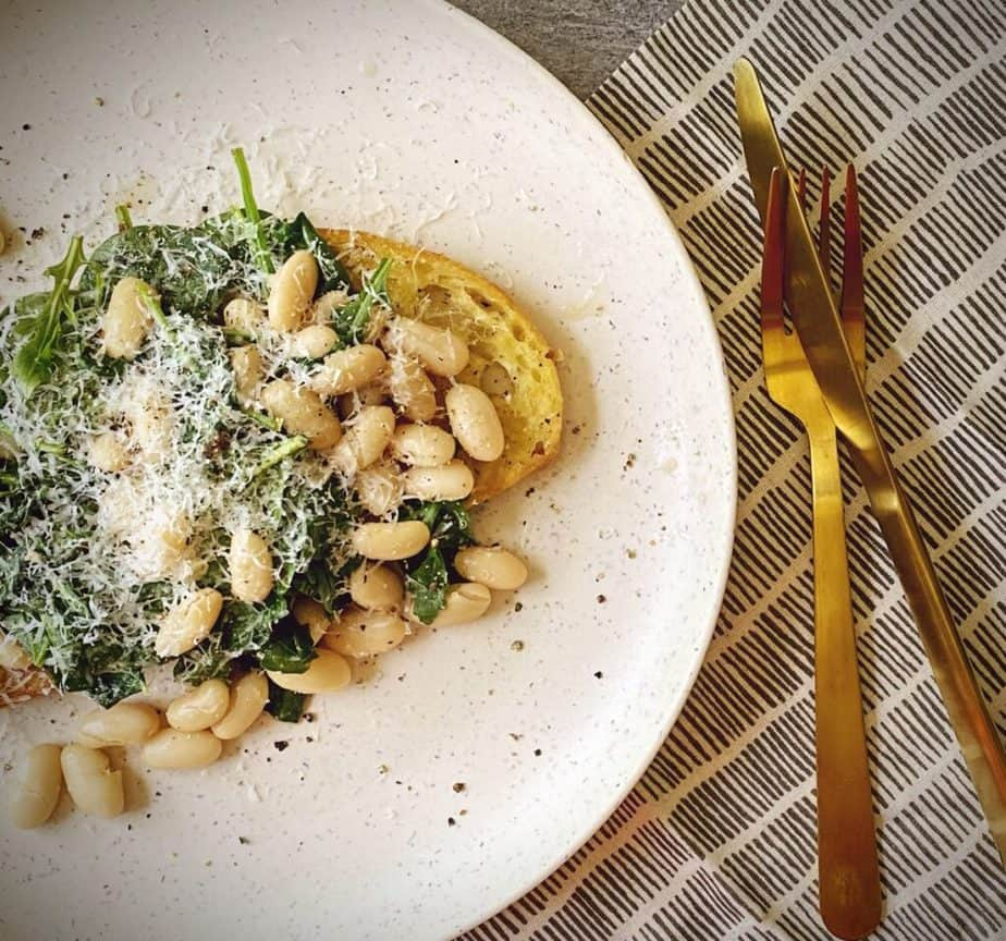 overhead shot of cannellini beans and wilted spinach mixture on toast topped with parmesan