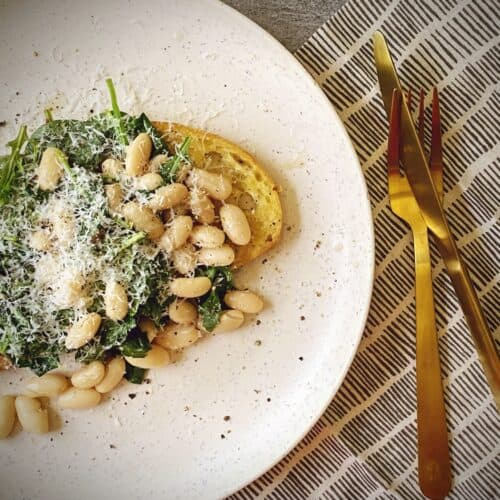 white beans and greens on toast topped with parmesan