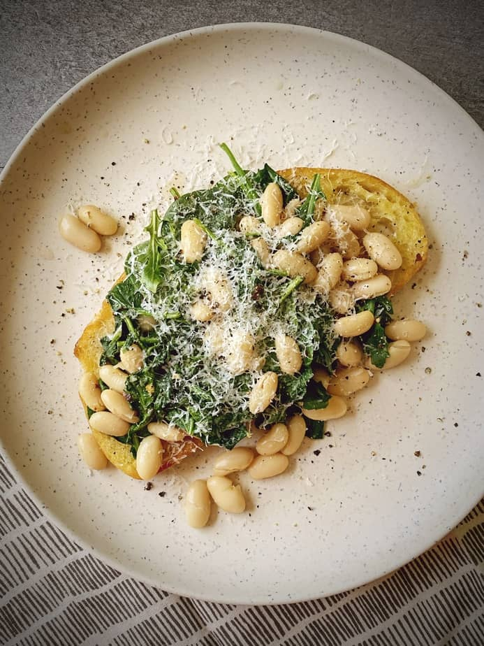overhead shot of beans and greens on toast with parmesan topping on a natural plate