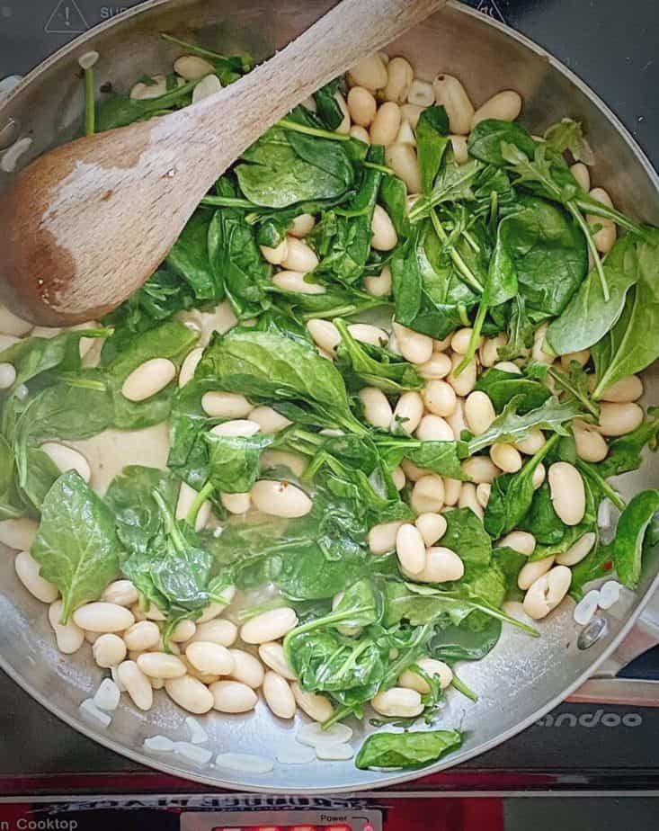 completed beans and wilted greens mixture in sauté pan with wooden spoon