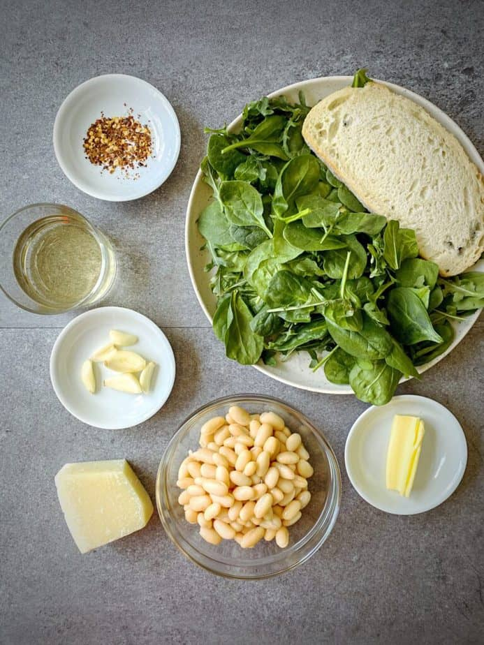 ingredients for beans and greens on toast laid out on a grey table