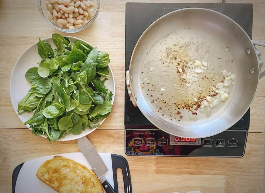 white wine, garlic and red pepper flakes simmering in sauté pan with beans, greens and fried toast on the side