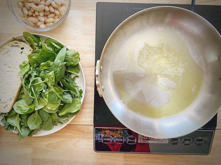 butter and oil heating in a pan to make a large format crouton for beans and greens on toast