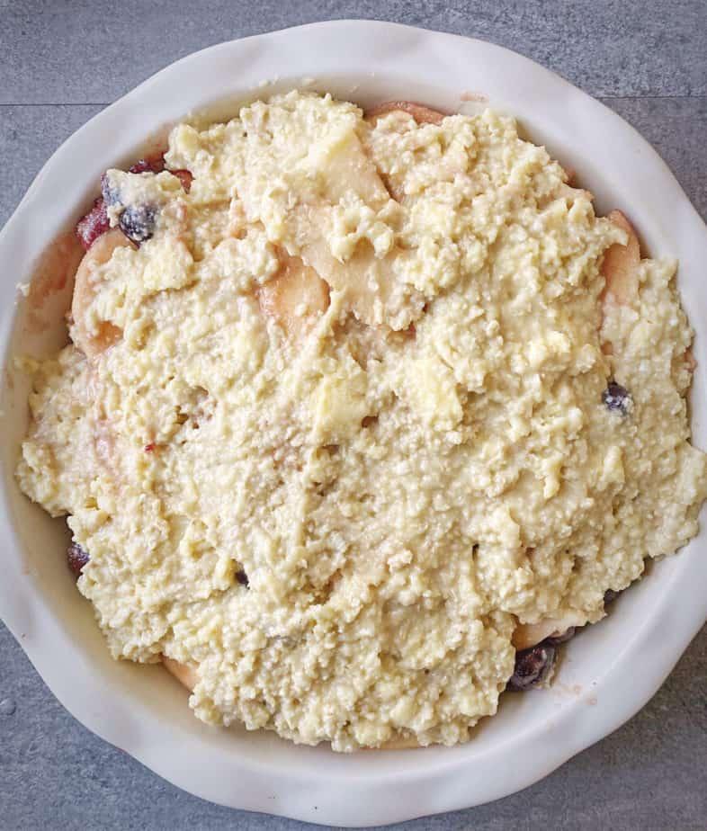 kodiak pancake mix cobbler topping spread atop fruit in an enamel pie dish
