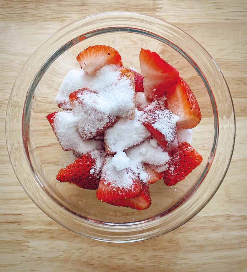 overhead shot of sugar and strawberries in a bowl