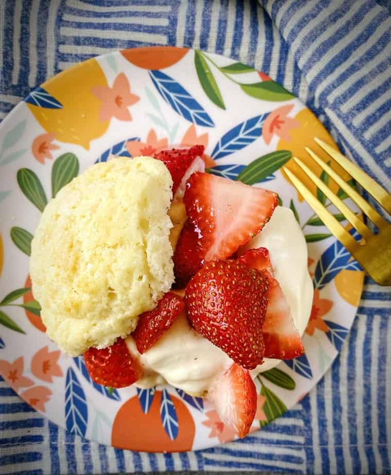 overhead shot of plated strawberry shortcakes on a floral dessert plate with a gold fork
