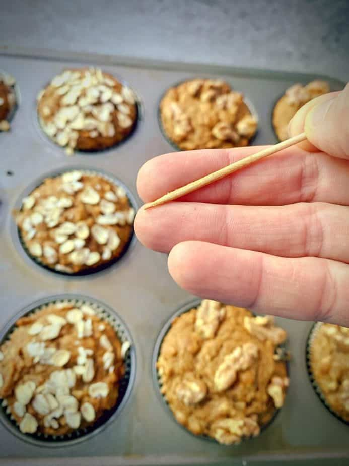 hand holding a toothpick above a tray of baked muffins, demonstrating that there are no crumbs left on the wood