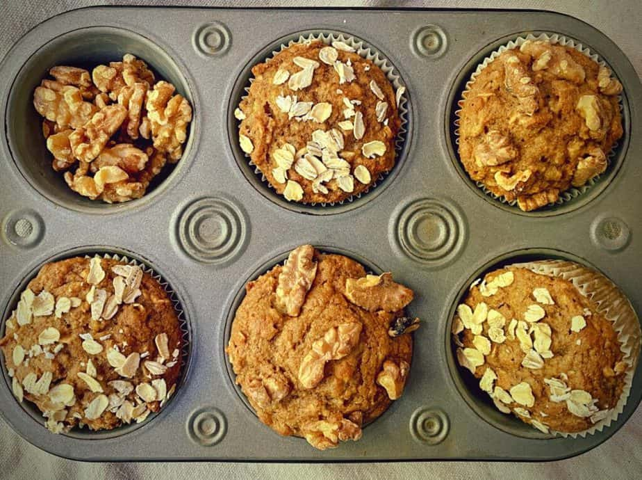 close up of a decorative half dozen muffin tin filled with walnut and oat topped muffins