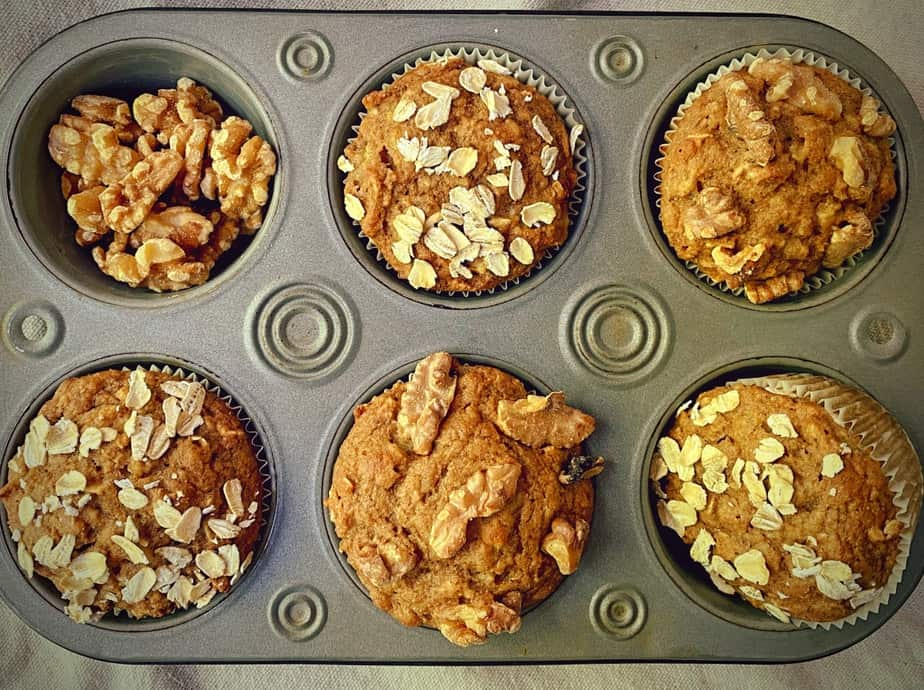 overhead shot of 5 muffins with a cup filled with walnuts