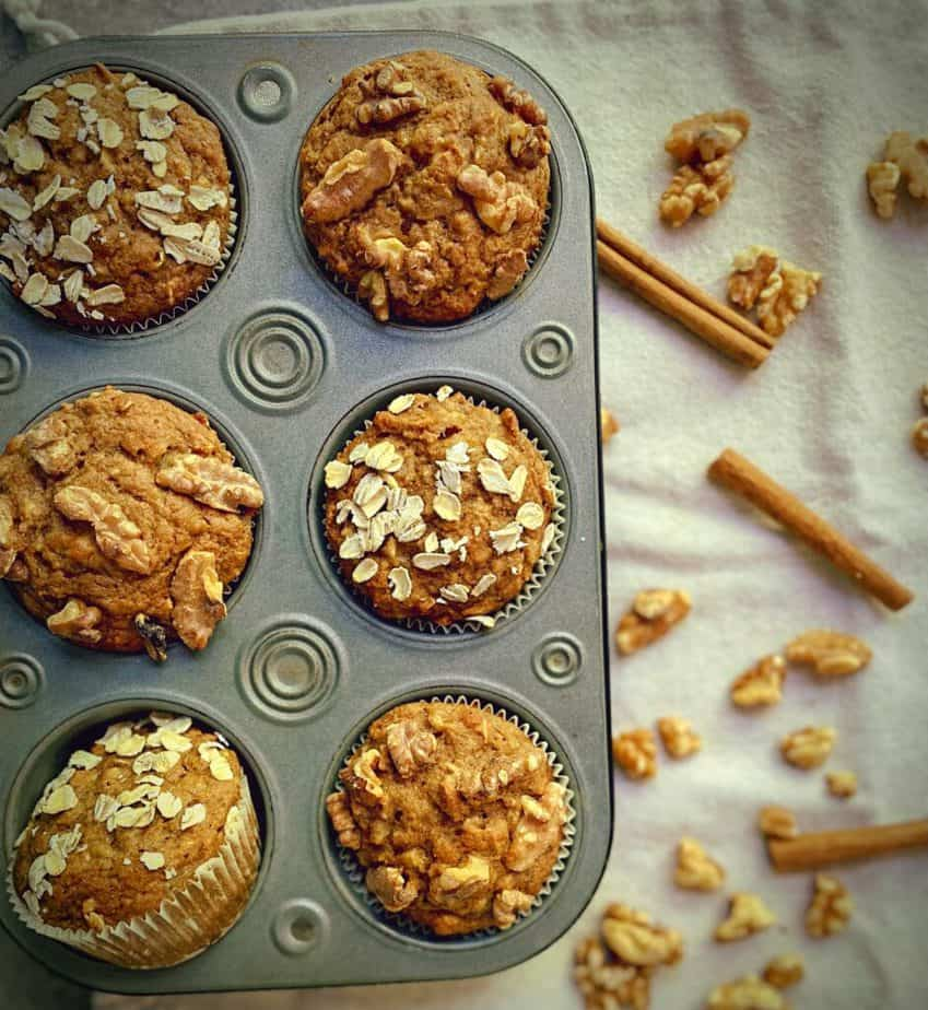 overhead shot of 6 healthy whole wheat muffins in a tin on a white tablecloth with canela sticks and walnuts