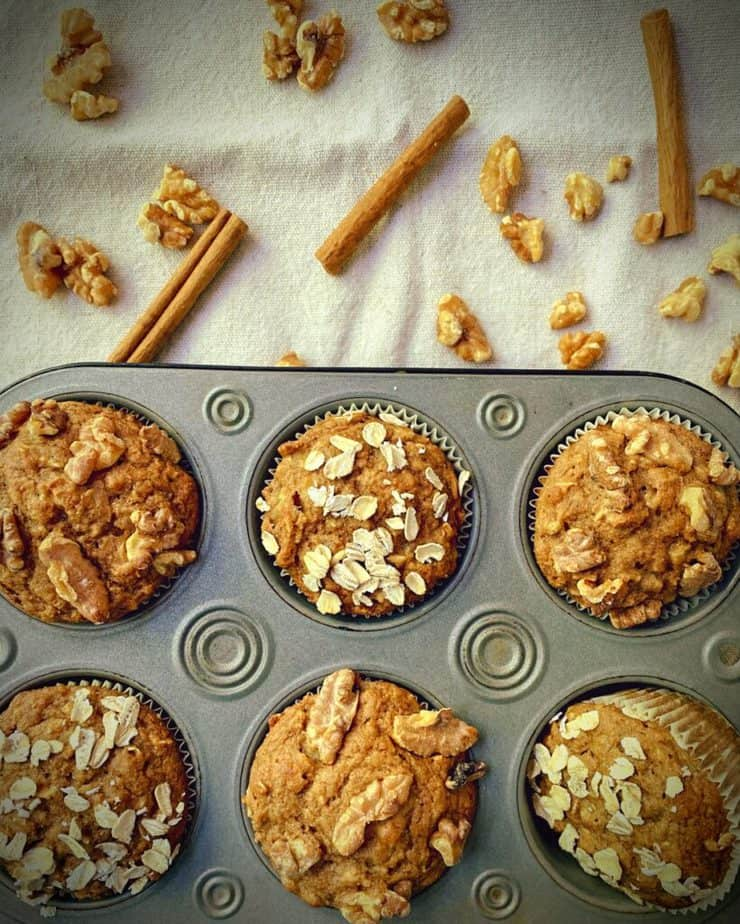 half dozen muffins in a silver baking tin on a table with scattered walnuts and canela sticks