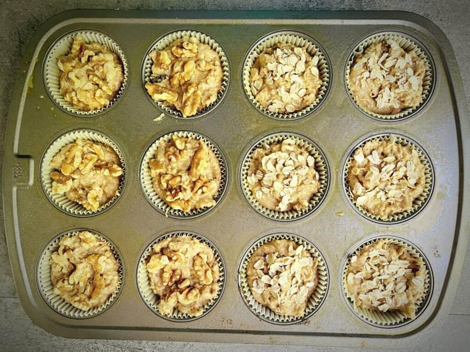 unbaked muffin batter topped with walnut pieces and rolled oats