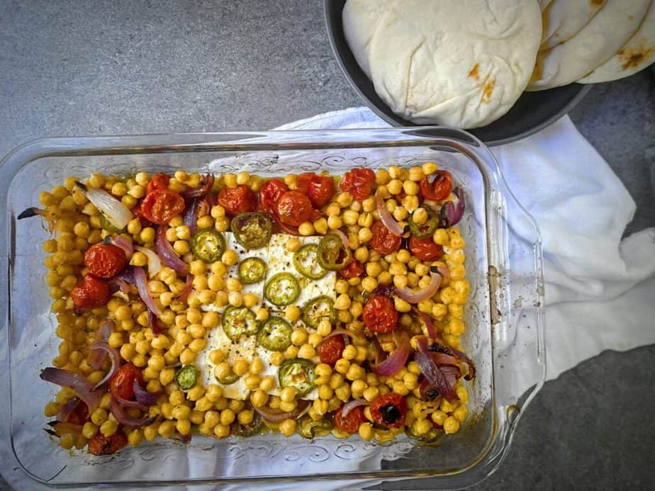 completed 9x13 of spicy mediterranean baked feta with chickpeas, tomatoes, onions, jalapeños and spices on a white cloth with a bowl of naan to the side