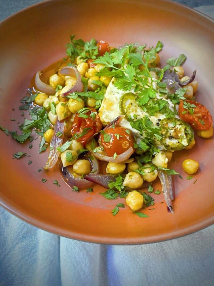 closeup shot of a bowl of mediterranean baked feta with tomatoes and chickpeas that has been garnished with fresh cilantro