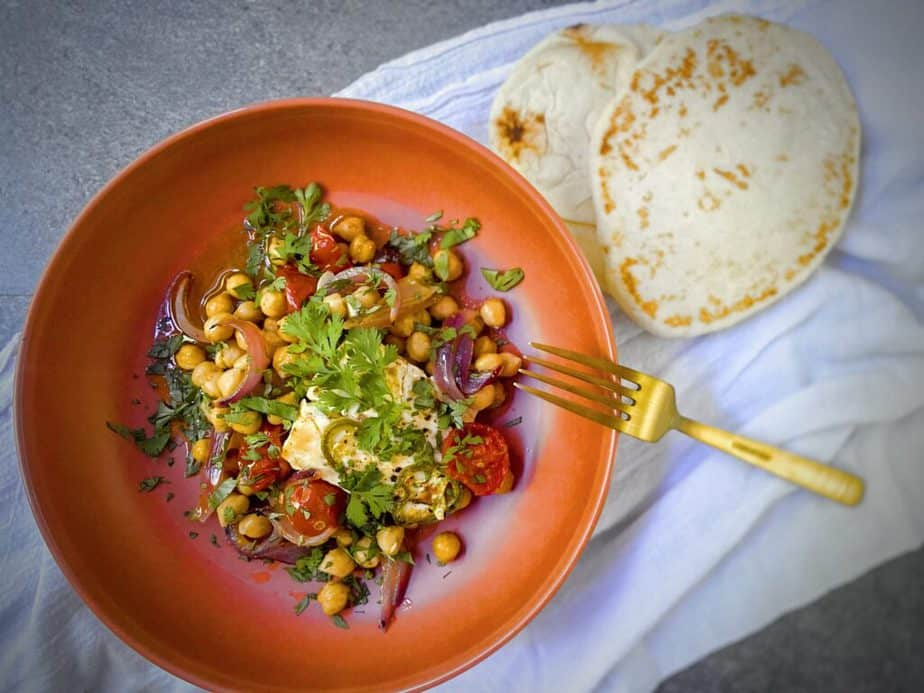 overhead shot of a terracotta bowl of spicy baked feta with tomatoes and chickpeas with a gold fork and two pieces of naan