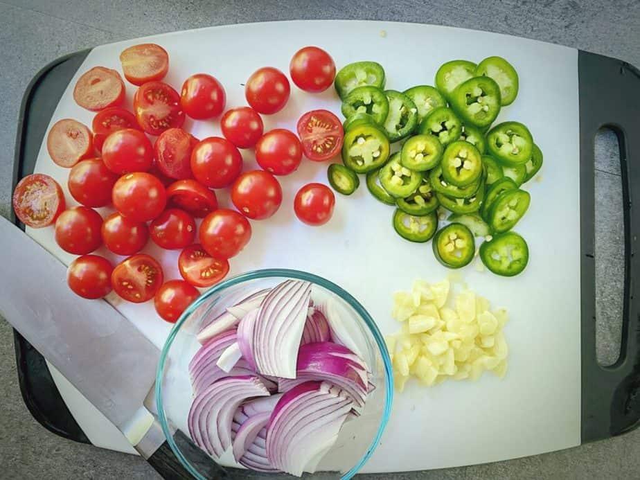 overhead shot of veggies for mediterranean baked feta - cherry tomatoes, sliced jalapeños, garlic and sliced onions