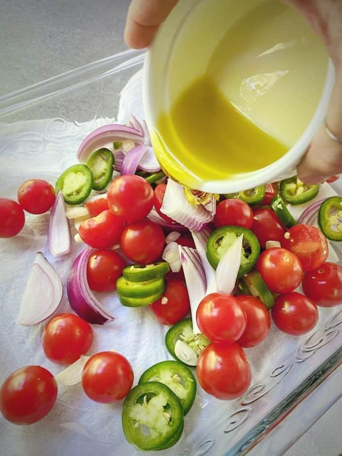 hand pouring olive oil onto prepped veggies for baked feta recipe