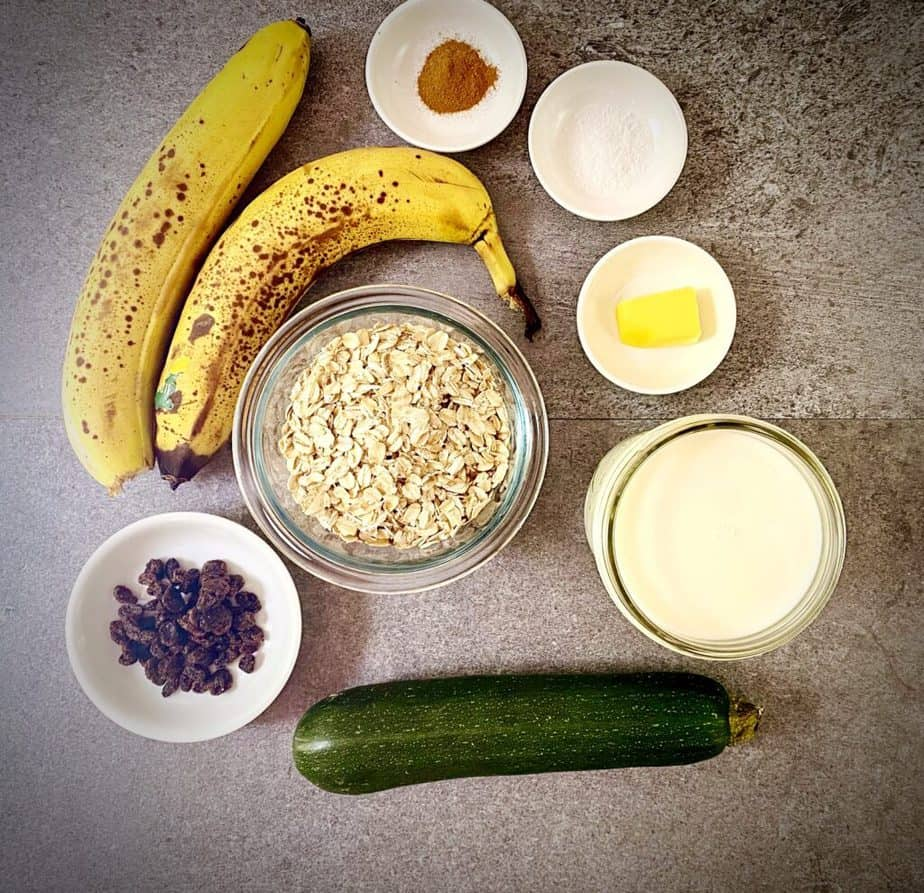 ingredients for zucchini bread oatmeal measured out into bowls on a grey table