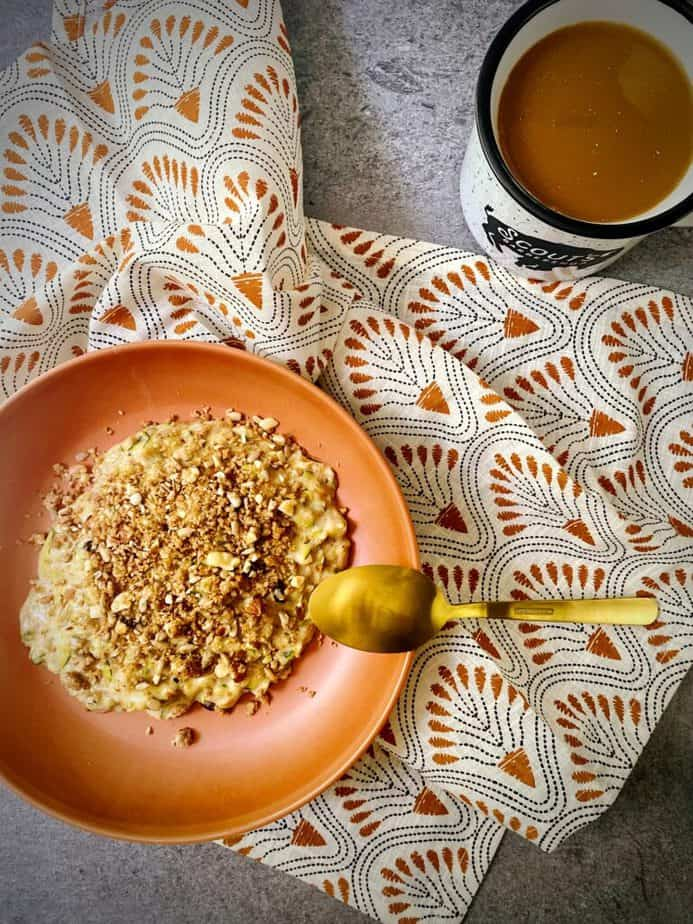overhead shot of zucchini bread oats in a burnt orange bowl with a gold spoon and a mug of coffee