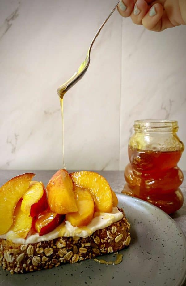 honey being drizzled onto a peach tartine from a height