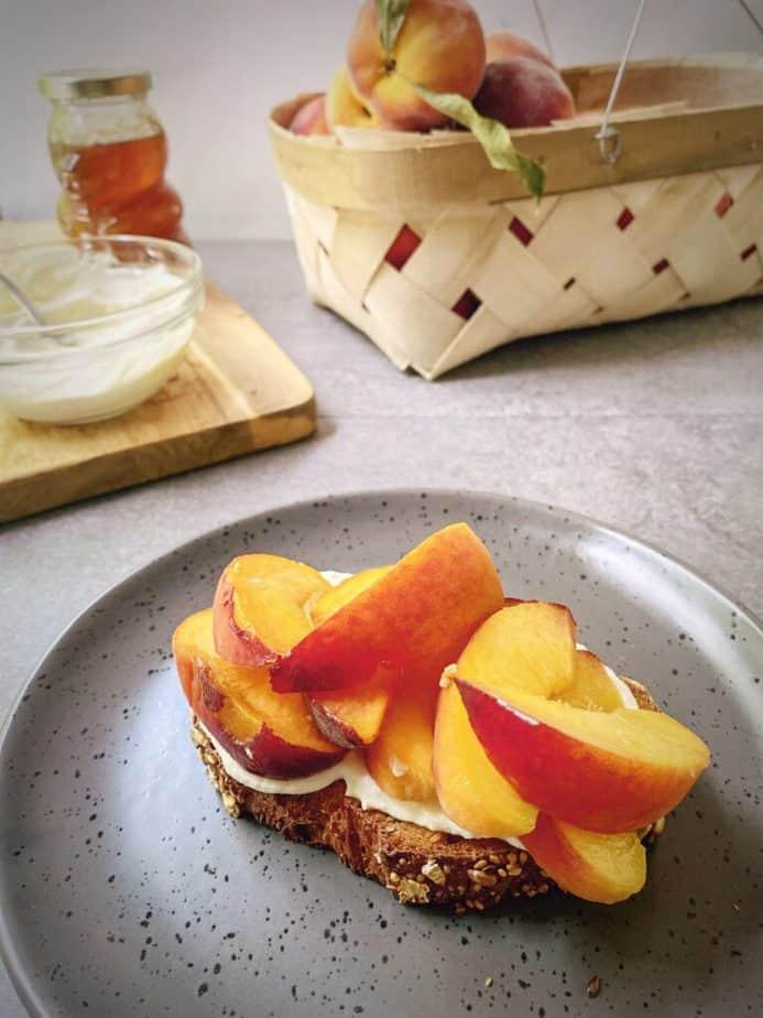 fresh sliced peaches added atop ricotta on toast