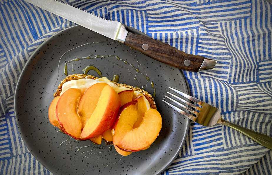 overhead shot of completed peach tartine on a grey plate with a wooden handled steak knife and silver fork