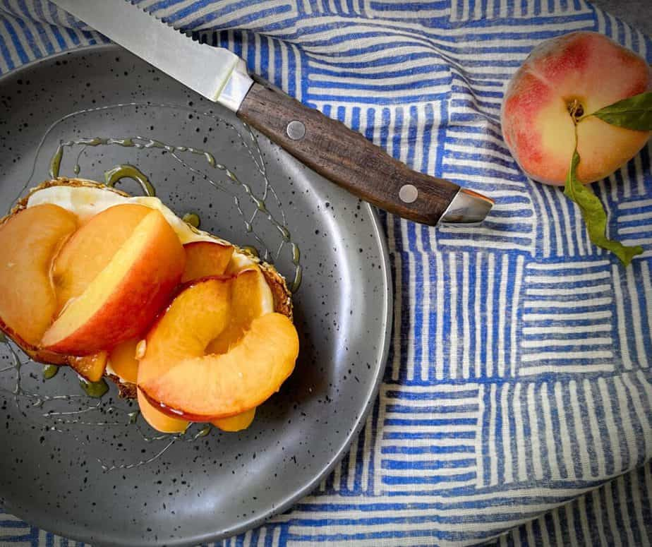 overhead shot of a grey speckled plate with a peach tartine with a wooden handled steak knife, a whole fresh peach and a blue and white striped cloth background