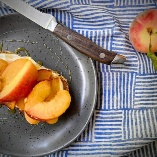 peach and ricotta tartine on a grey speckled plate with a wooden handled steak knife and a whole peach