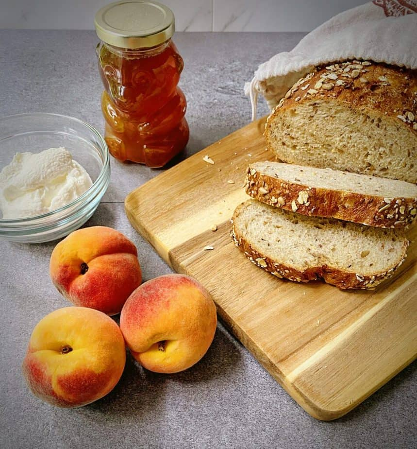 ingredients for making marché style peach tartine on a grey table