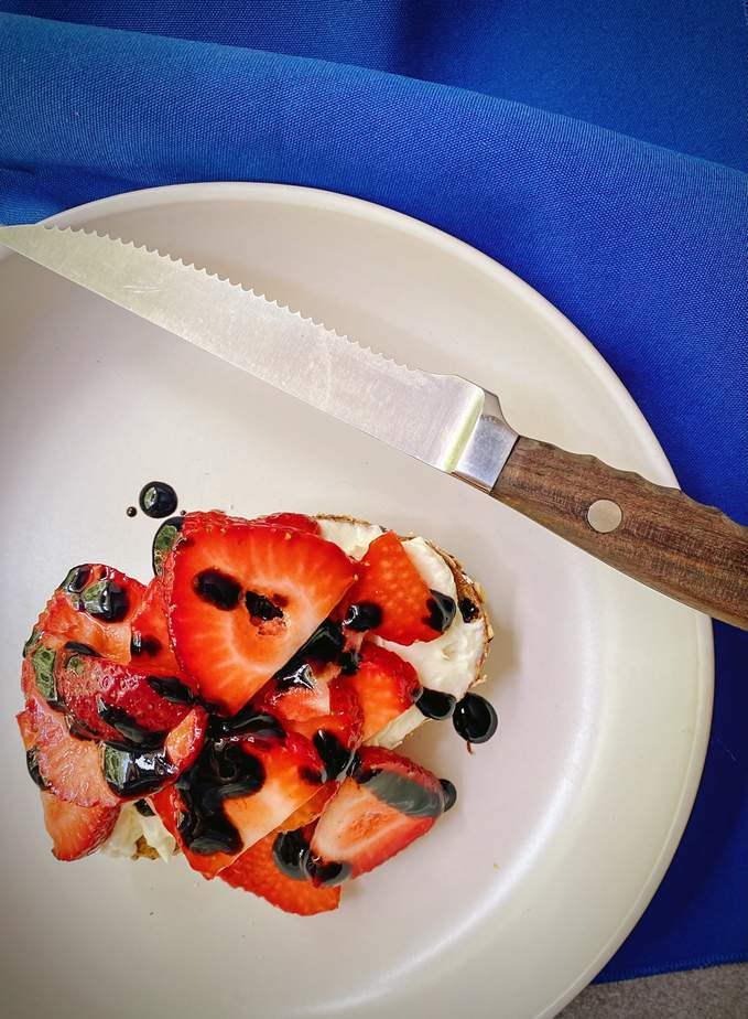 overhead shot of strawberry tartine on a white plate with a drizzle of balsamic reduction and a royal blue cloth