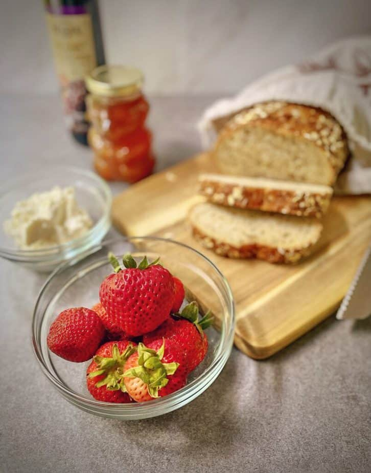 ingredients for strawberry tartine laid out on a table - bowl of strawberries, sliced multigrain bread on a cutting board, mascarpone cheese, honey bear and bottle of balsamic vinegar