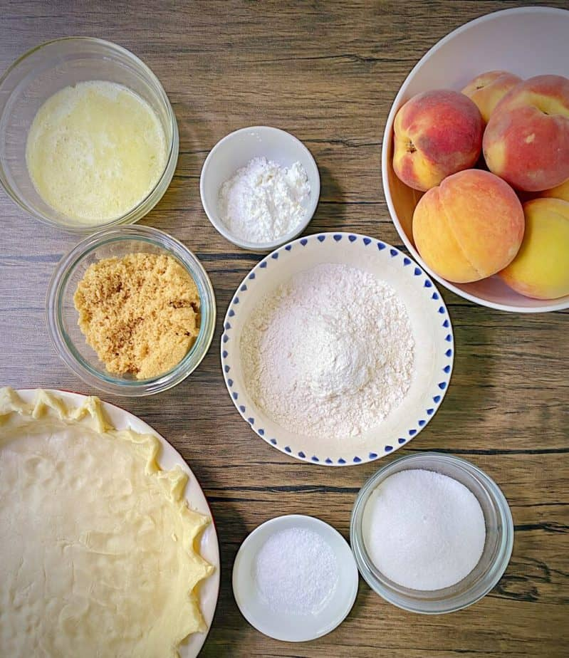 ingredients for making peach crumble pie measured out into bowls on a wooden table